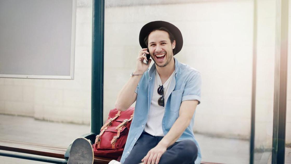 Парень говорит по телефону и смеется