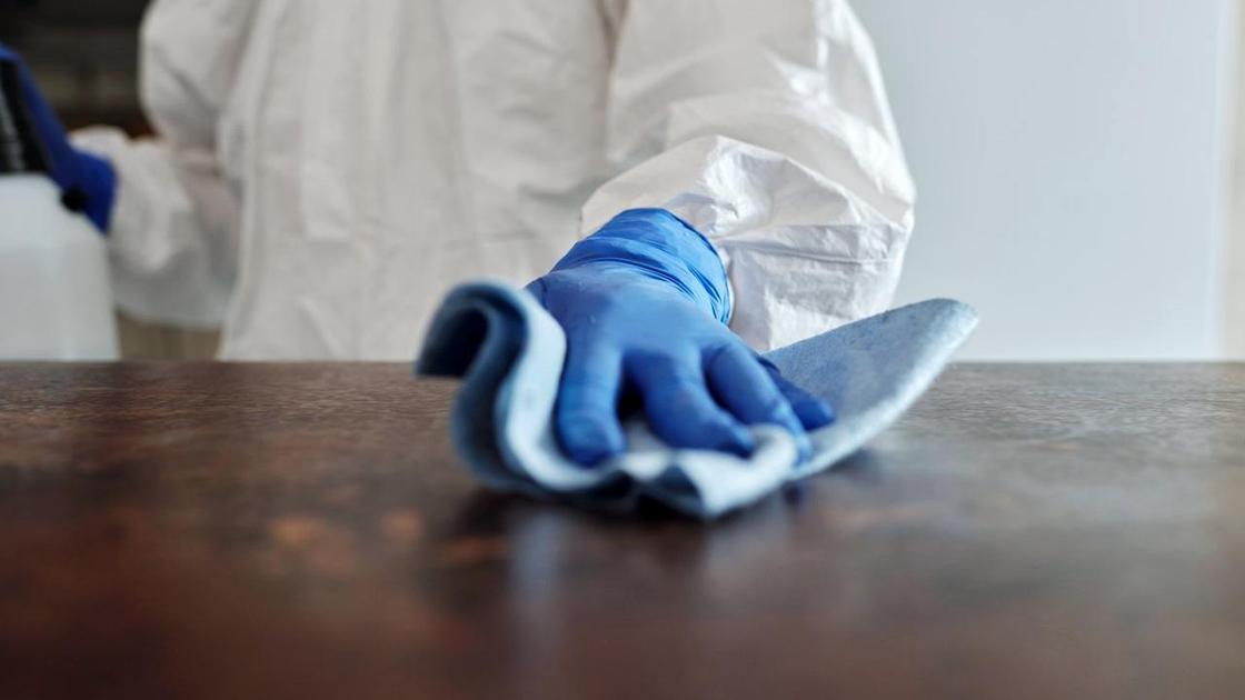 Санитар обрабатывает поверхность неизвестным веществом