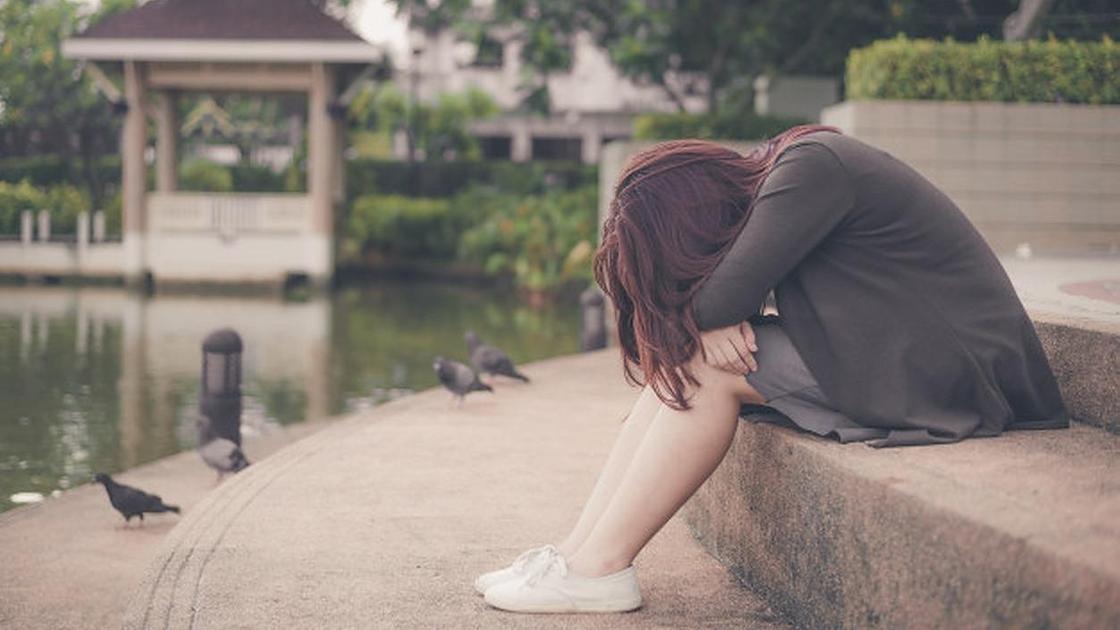 Девушка сидит, опустив голову на руки, на набережной