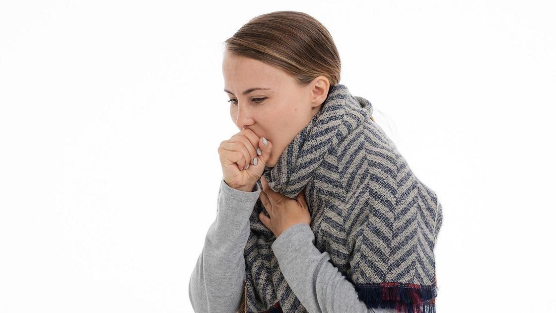 Девушка в шарфе кашляет