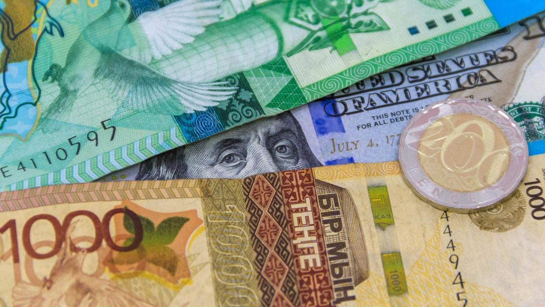Доллар США лежит под купюрами тенге