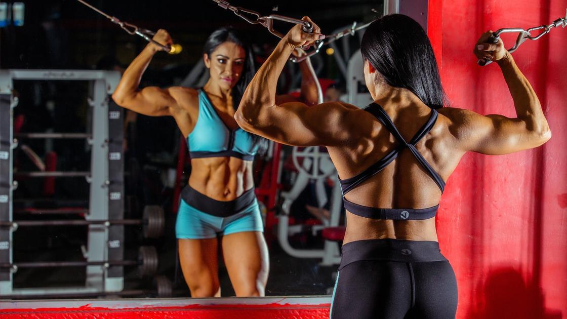 Женщина в тренажерном зале смотрит в зеркало