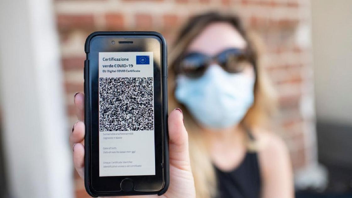Девушка в маске держит телефон с паспортом вакцинации