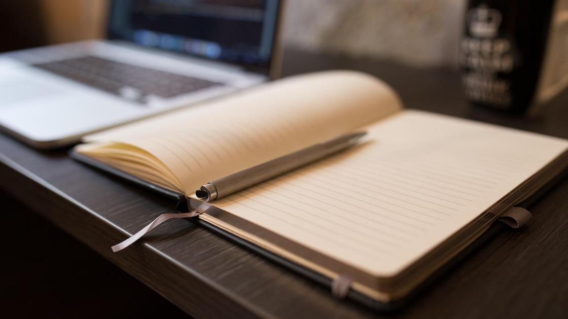 Тетрадь, ручка и ноутбук на столе