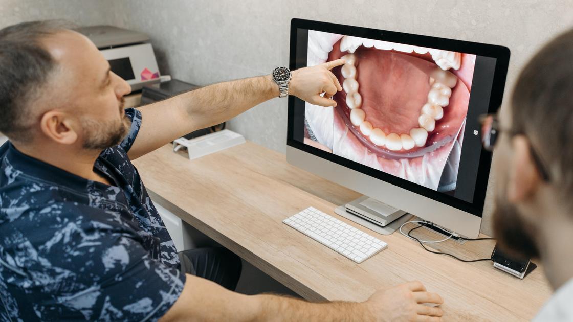 Стоматолог показывает снимок полости рта пациенту