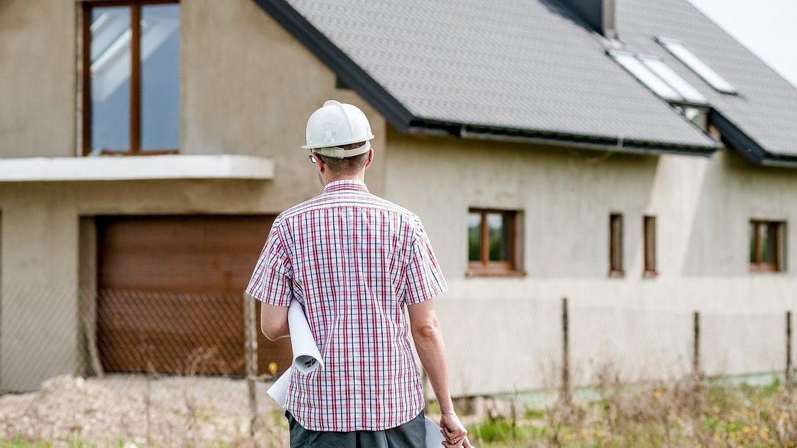 Мужчина в строительной каске идет в сторону дома