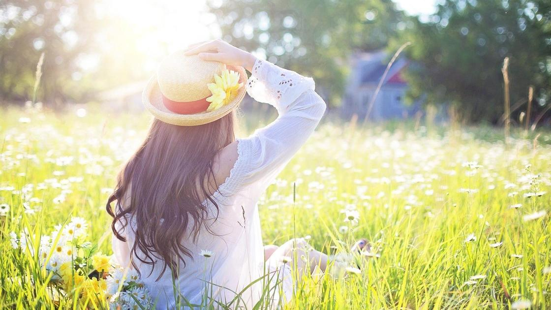 девушка сидит в цветах на поляне