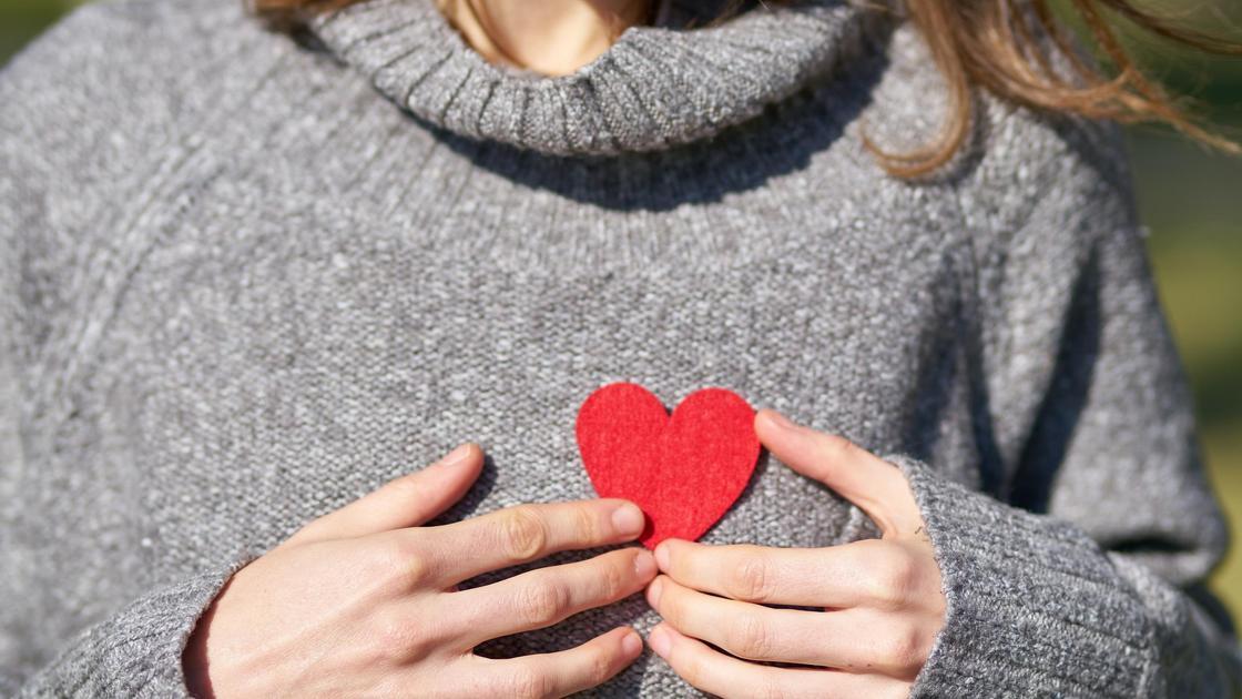 Девушка в сером свитере держит красное сердце