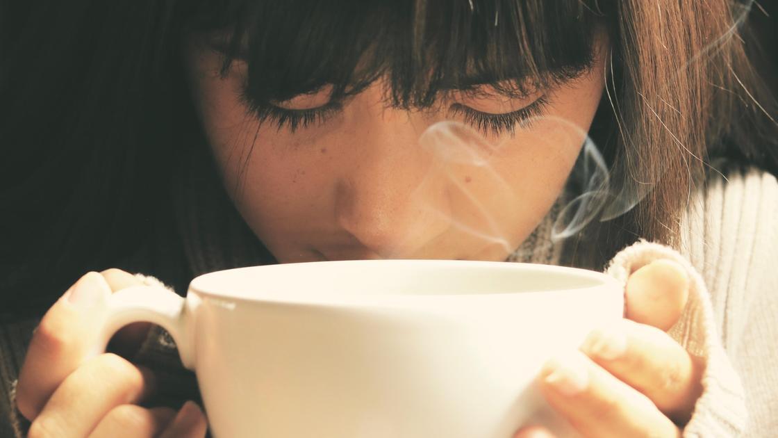 Девушка вдыхает аромат напитка