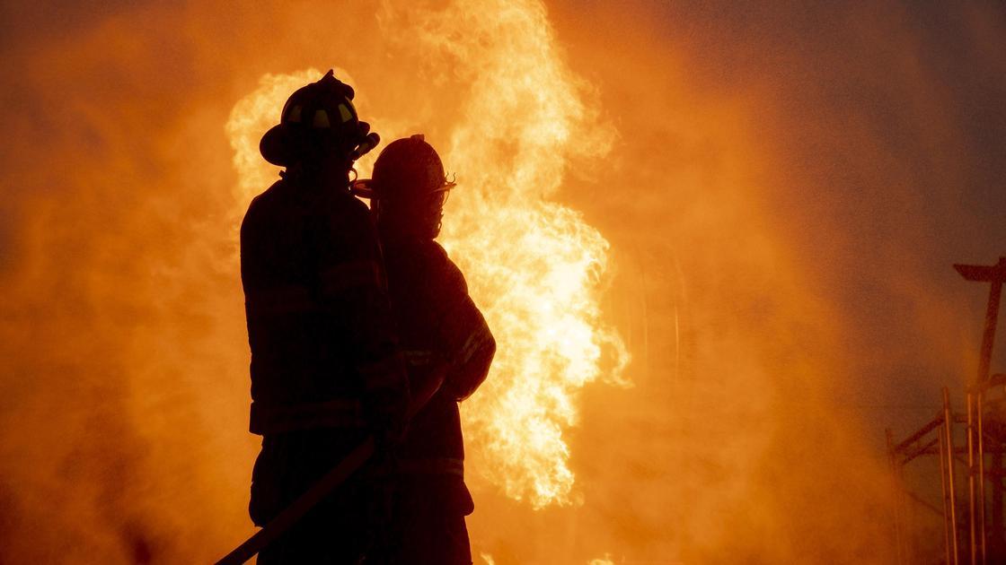 Пожарные на фоне пламени