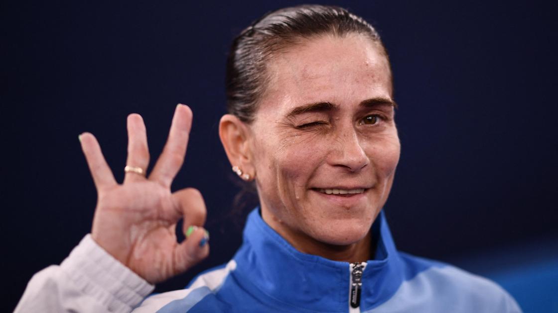 Женщина подмигивает глазом и держит три пальца вверх