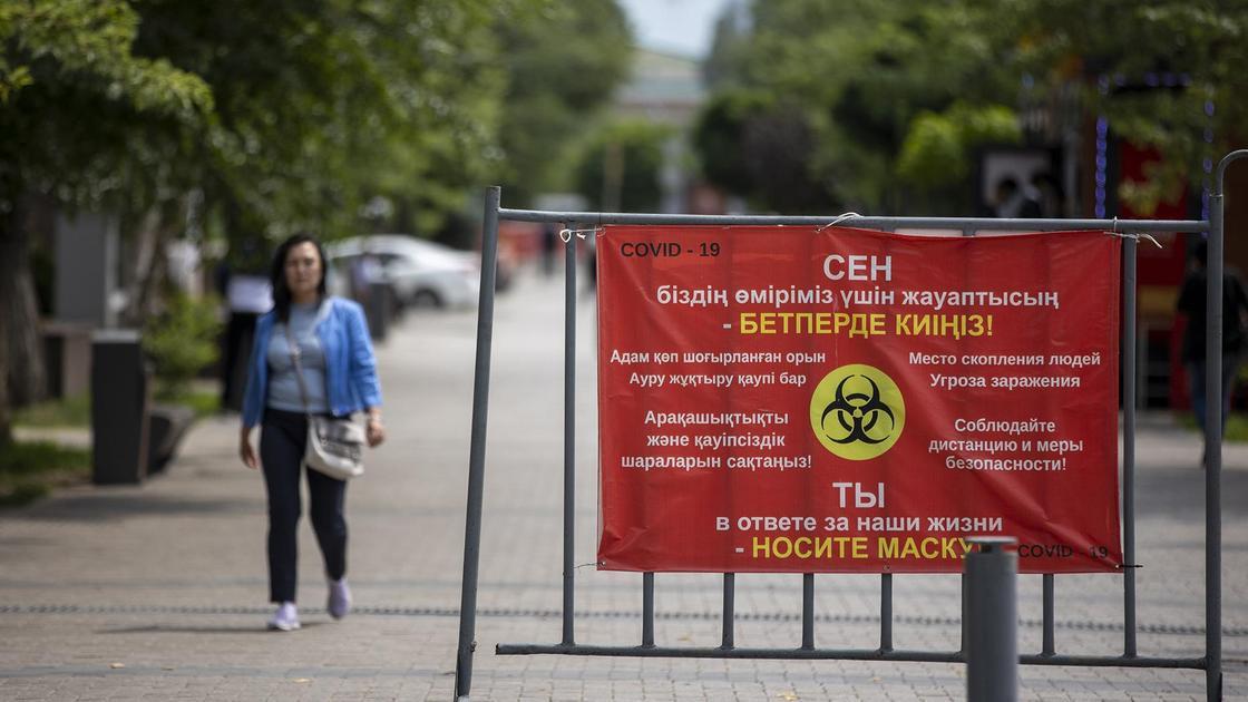 Женщина идет по улице на фоне баннера с предупреждением о COVID-19
