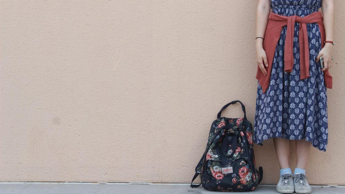 Девушка стоит рядом с рюкзаком