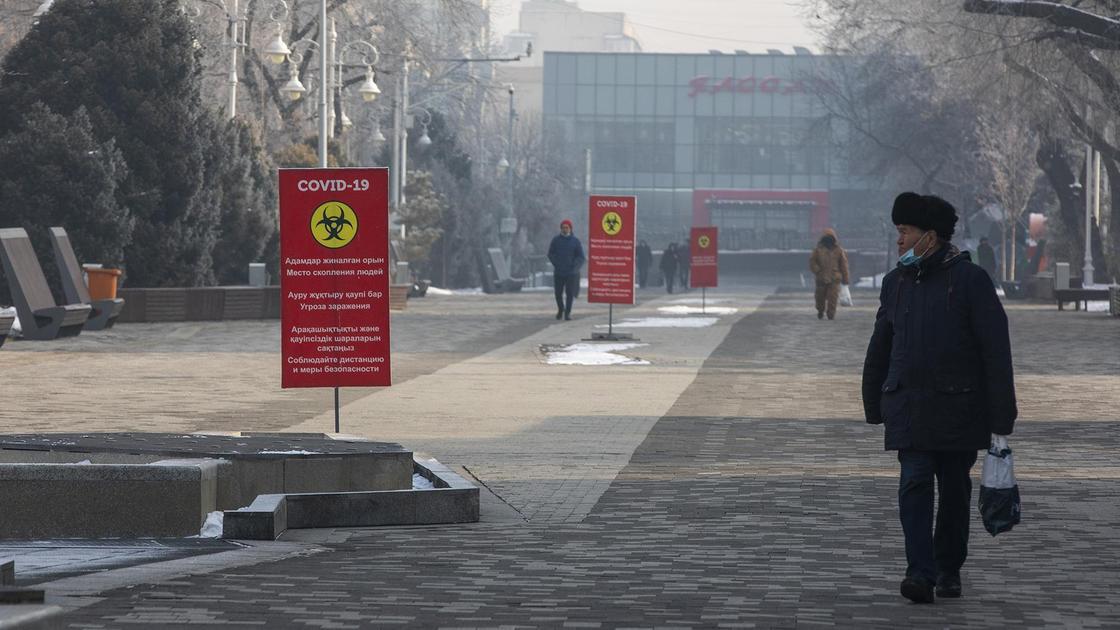 Люди идут по улице с баннерами с информацией по коронавирусу в Алматы
