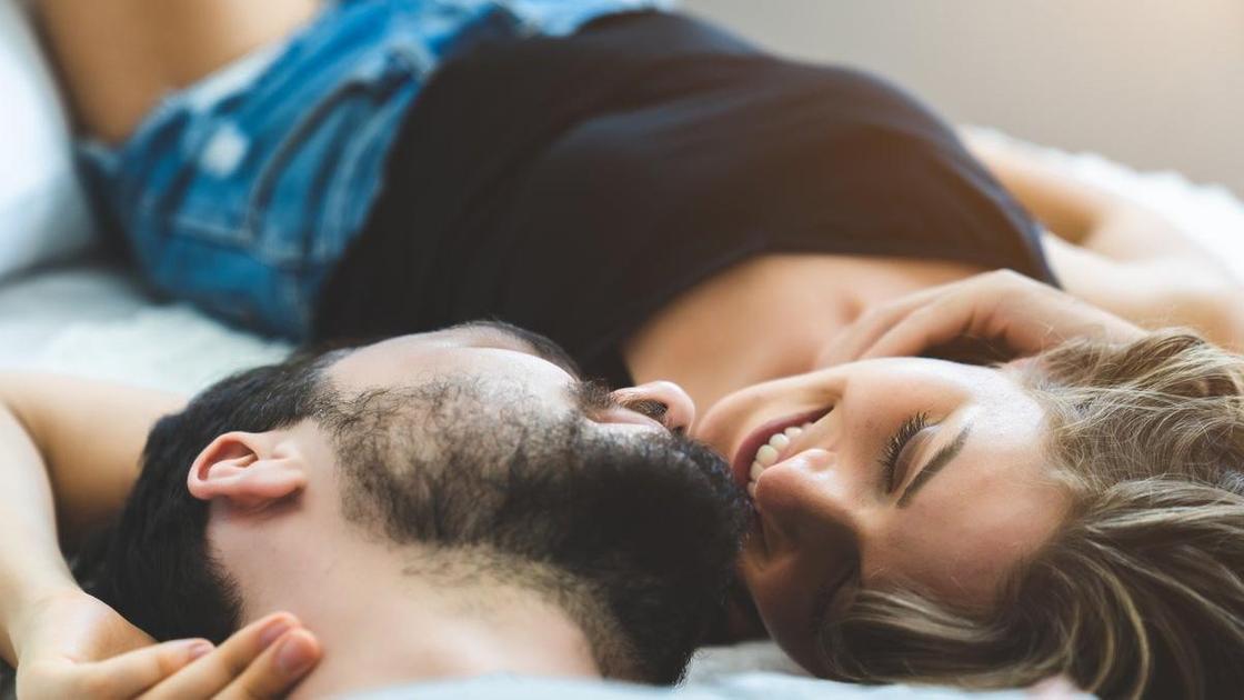 Девушка и парень в постели улыбаются