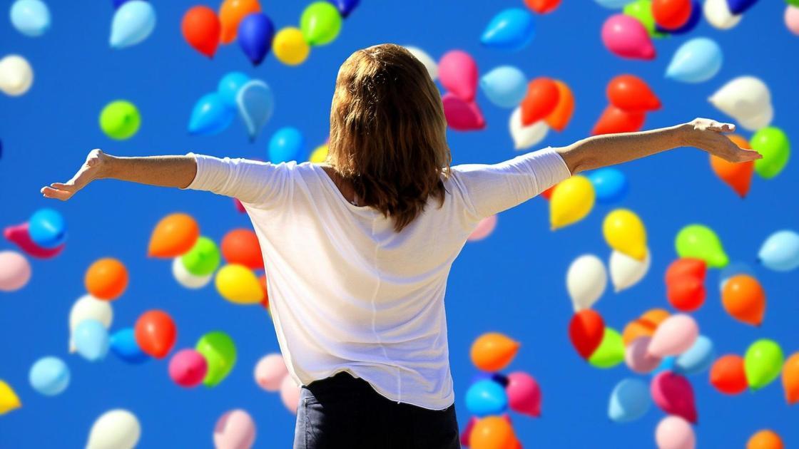 Девушка на фоне летящих в небе воздушных шаров