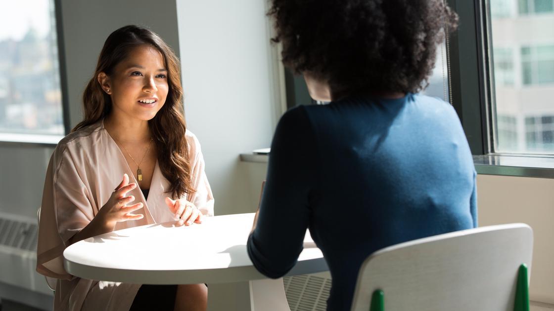 Две девушки беседуют, сидя за столом