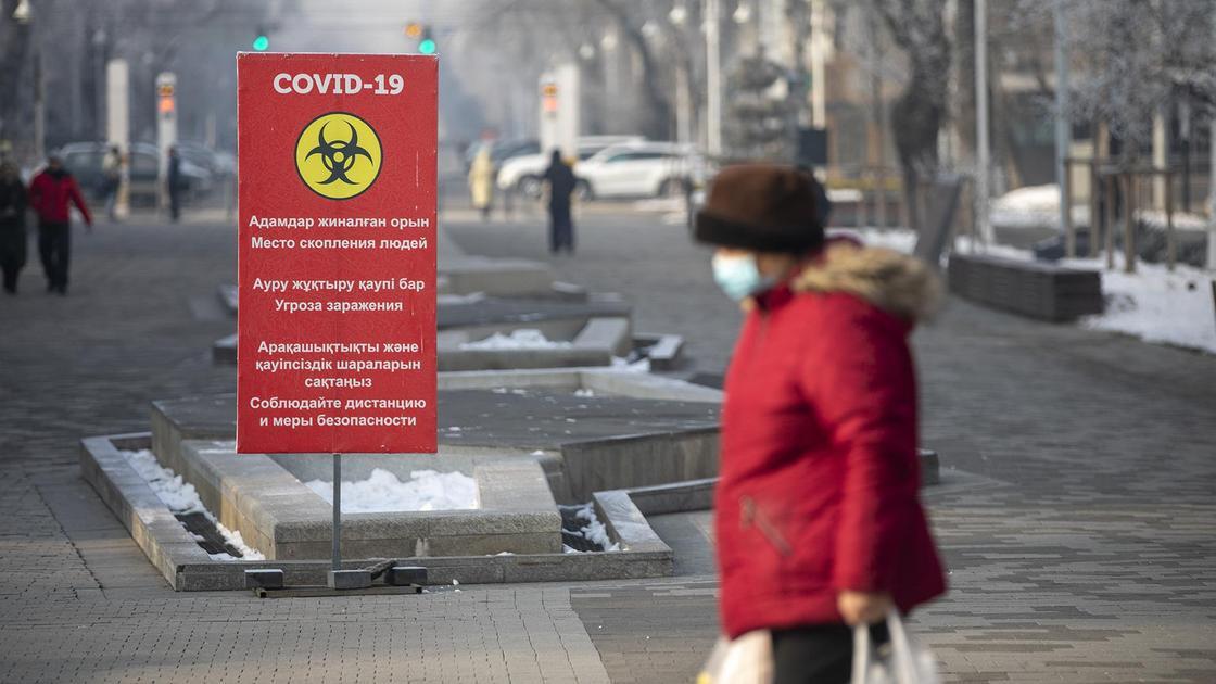 Женщина в маске идет по улице в Алматы
