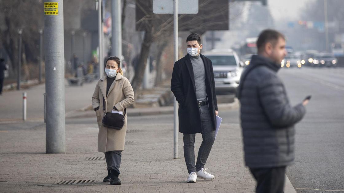 Три человека в теплой одежде стоят на остановке