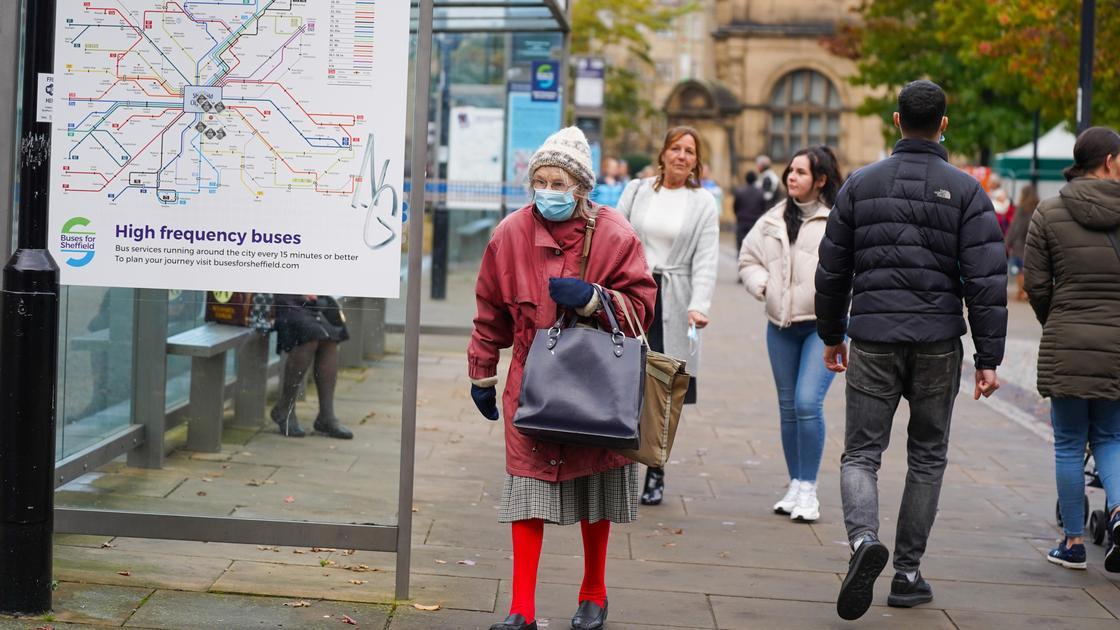 пожилая женщина идет по улице в маске