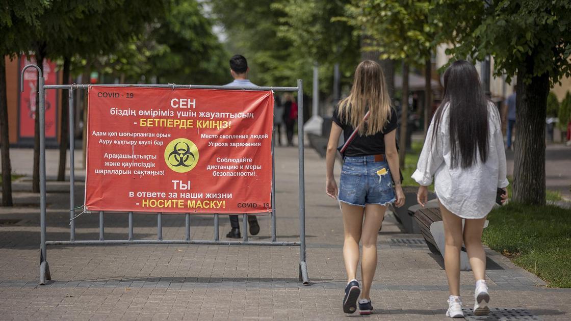 Две девушки идут мимо баннера с предупреждением о COVID-19