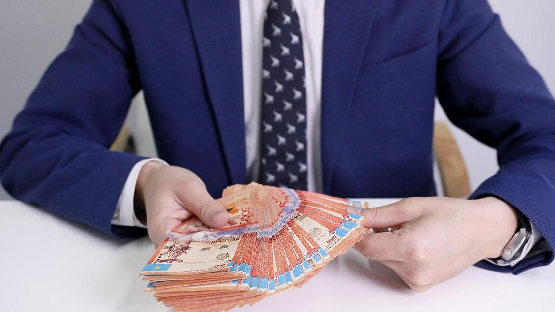 Мужчина в костюме держит в руках пачку денег
