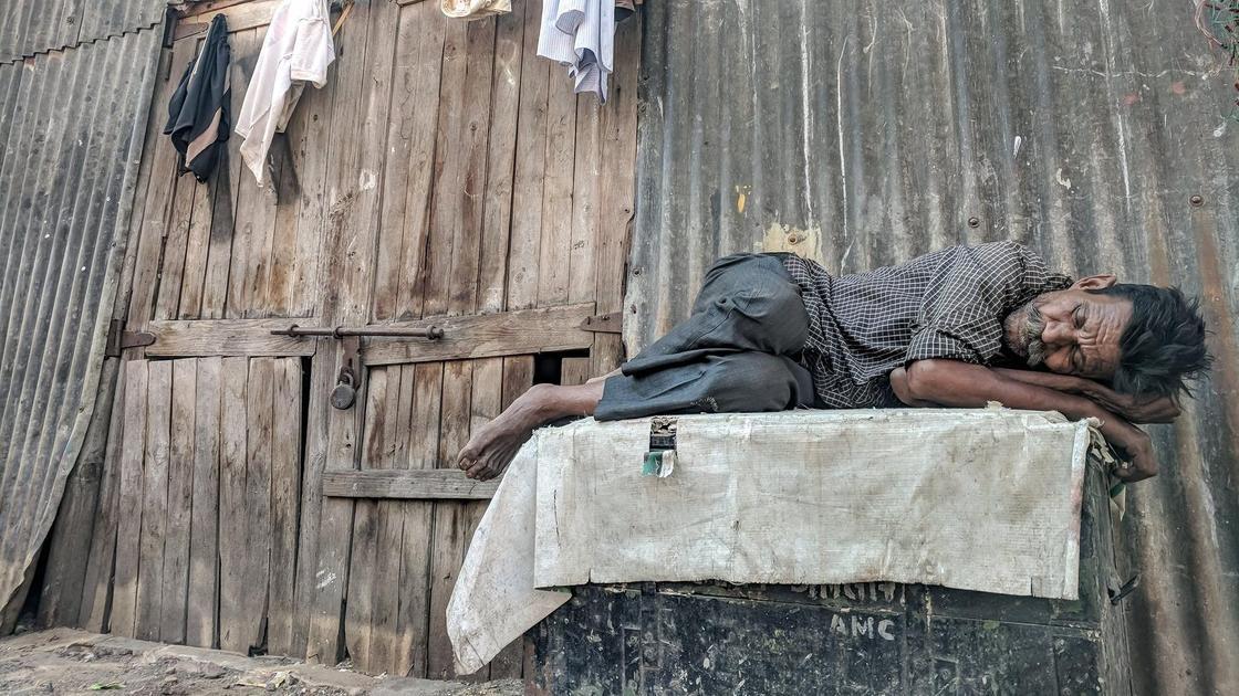 Мужчина в грязной одежде спит на улице возле сарая
