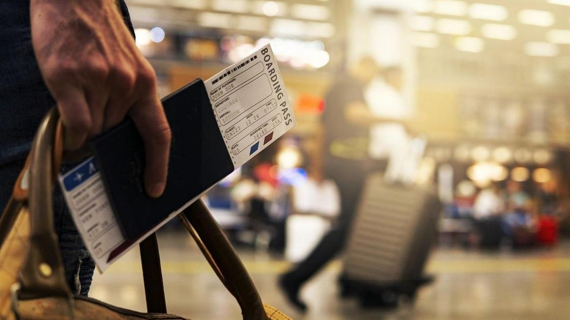 Мужчина с билетом стоит в аэропорту