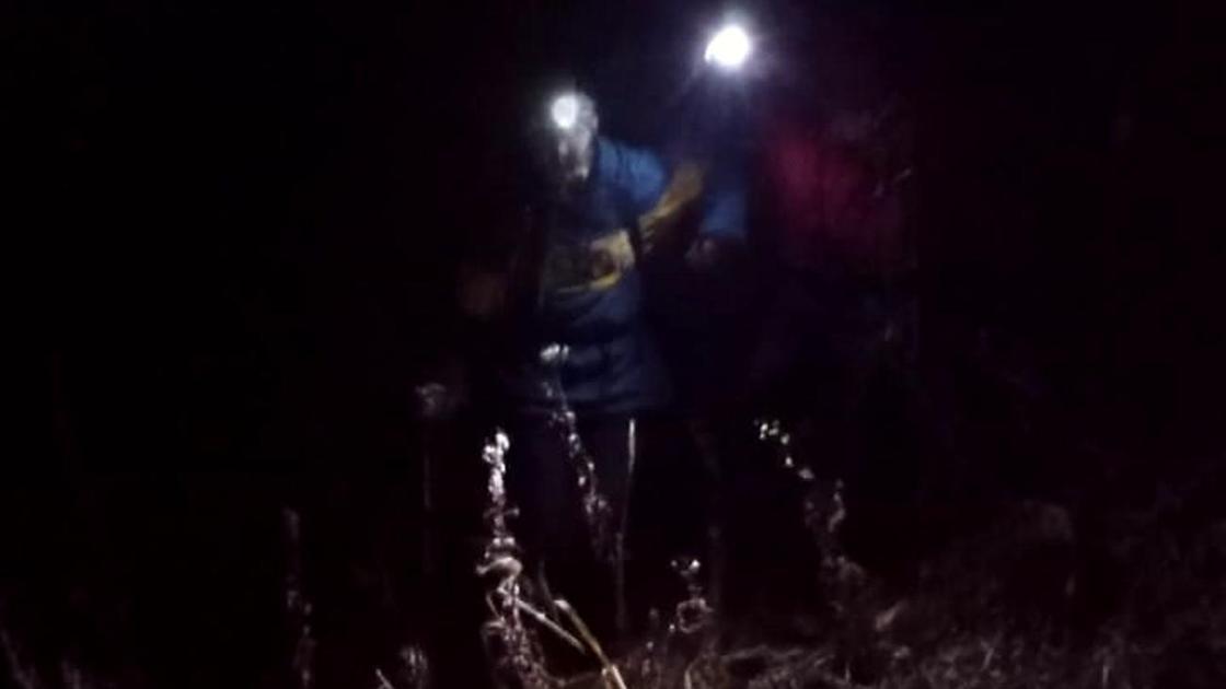 Спасатели сопровождают девушку при спуске с гор