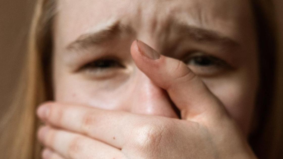 Девочка плачет и закрывает лицо рукой