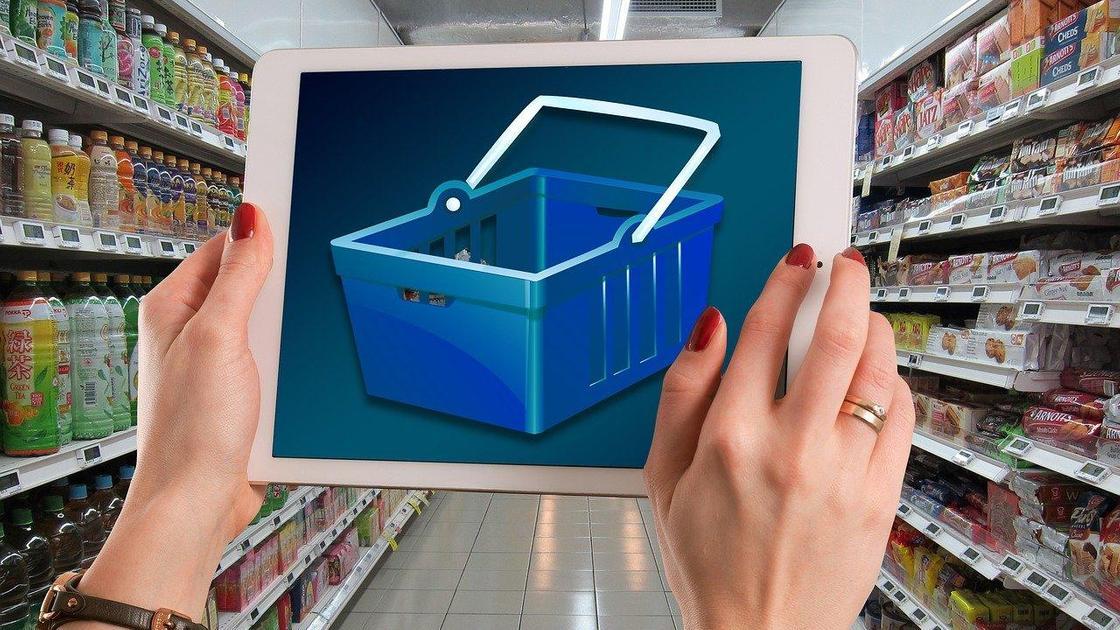 Женщина в супермаркете держит картинку с корзиной