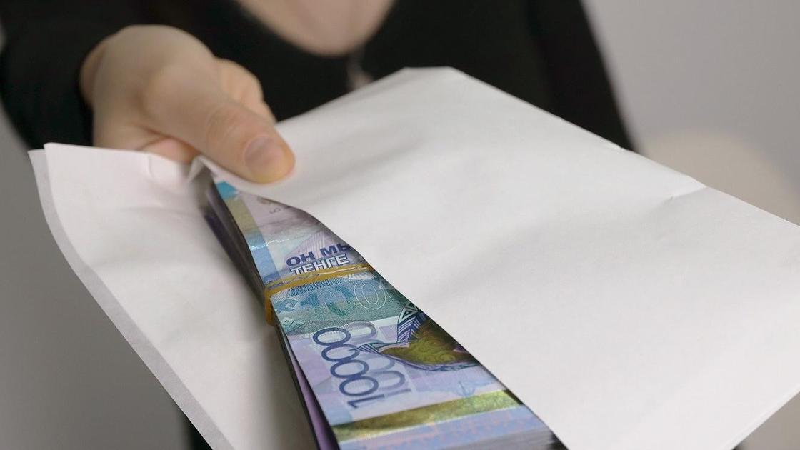 Женщина держит конверт с деньгами