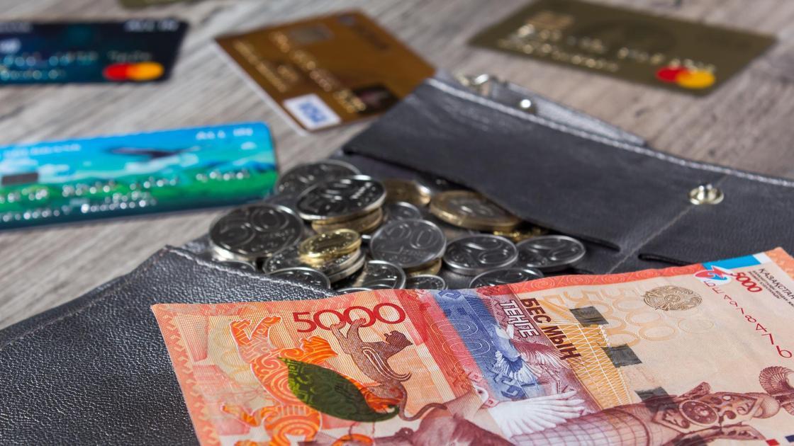 На столе лежат деньги, монеты и банковские карты