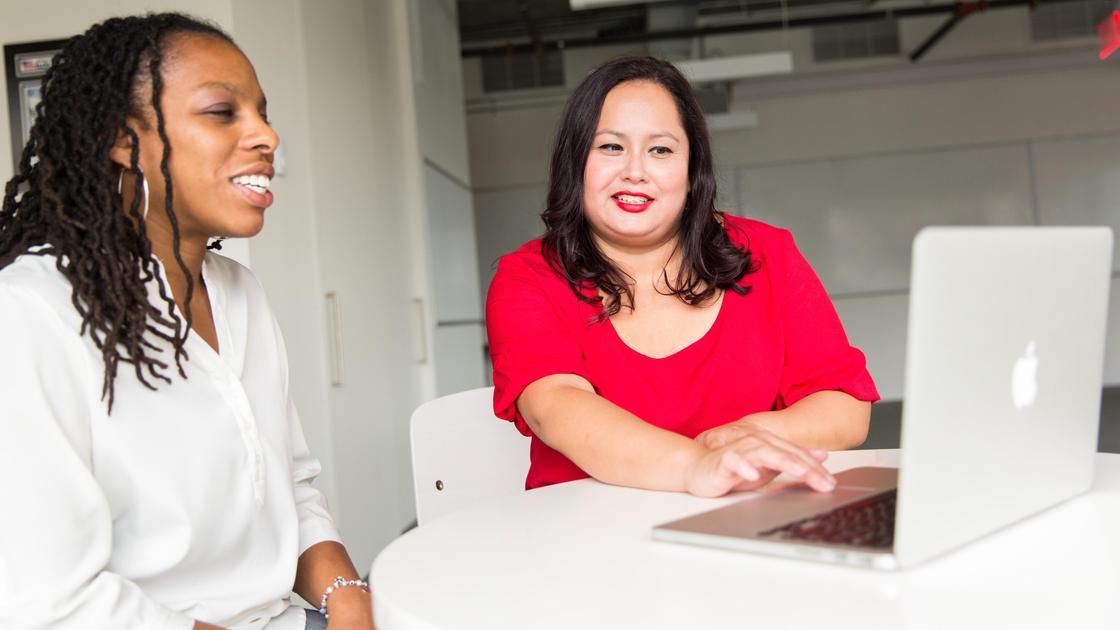Две женщины сидят за столом и смотрят на экран ноутбука