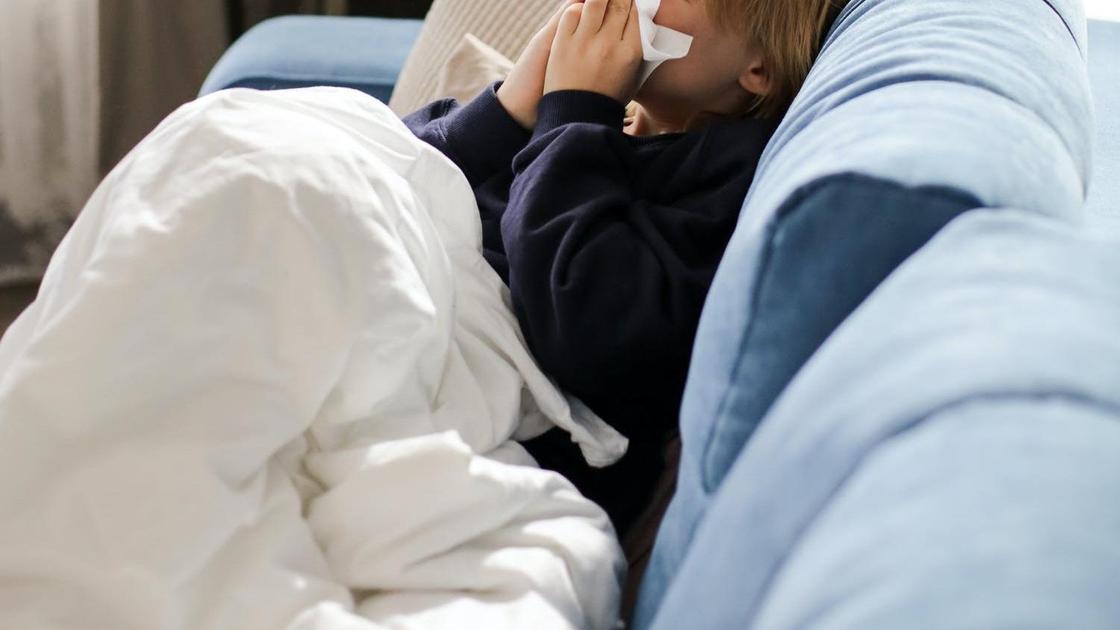 Больной ребенок вытирает нос платком