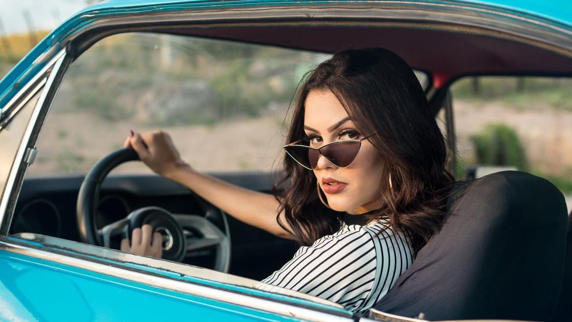 Женщина в солнцезащитных очках за рулем голубой машины