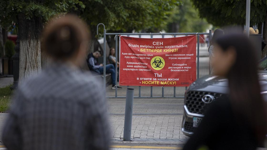 Люди идут по улице на фоне баннера с предупреждением о COVID-19