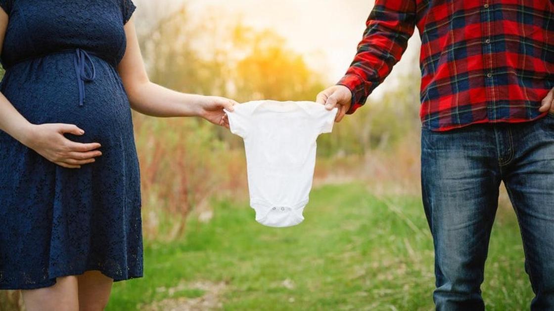 беременная женщина и будущий отец держат детскую одежду