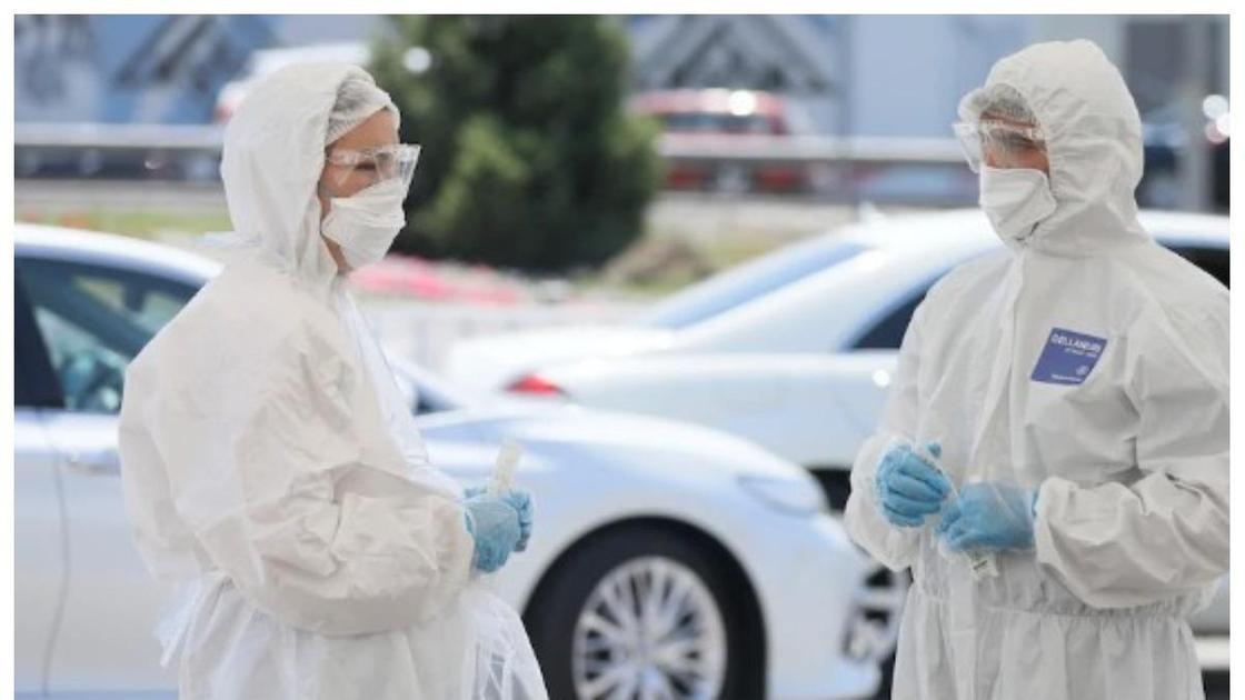 медики в защитных костюмах стоят на улице