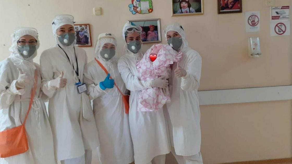 Медики стоят в палате с маленьким ребенком