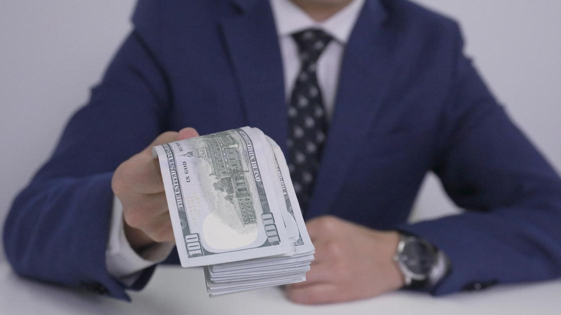 Мужчина держит пачку денег в руке