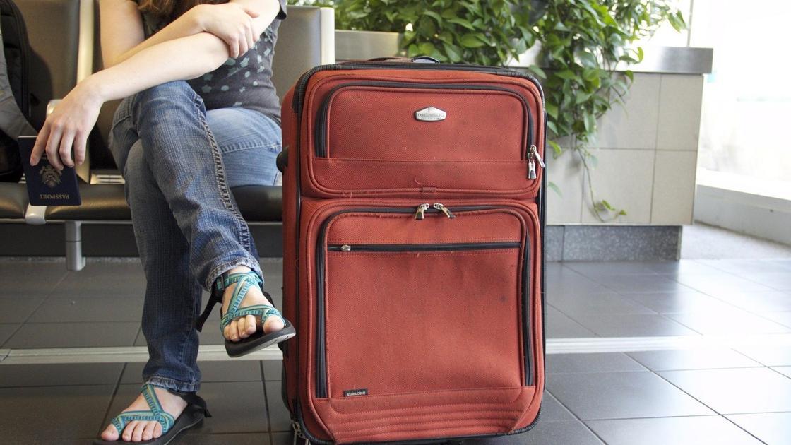 девушка с багажом сидит в аэропорту