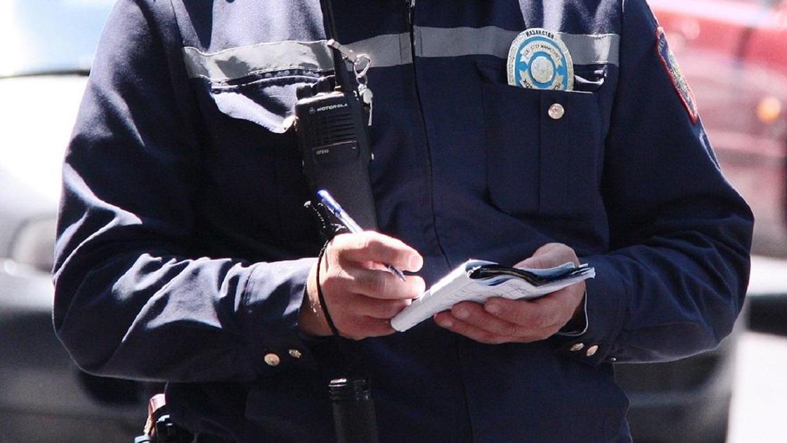 Полицейский что-то записывает в свой блокнот