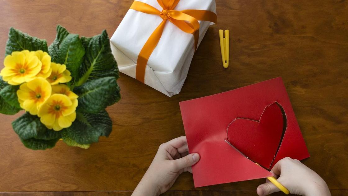 Из красной бумаги вырезают сердечко, упакованный подарок, фиалки