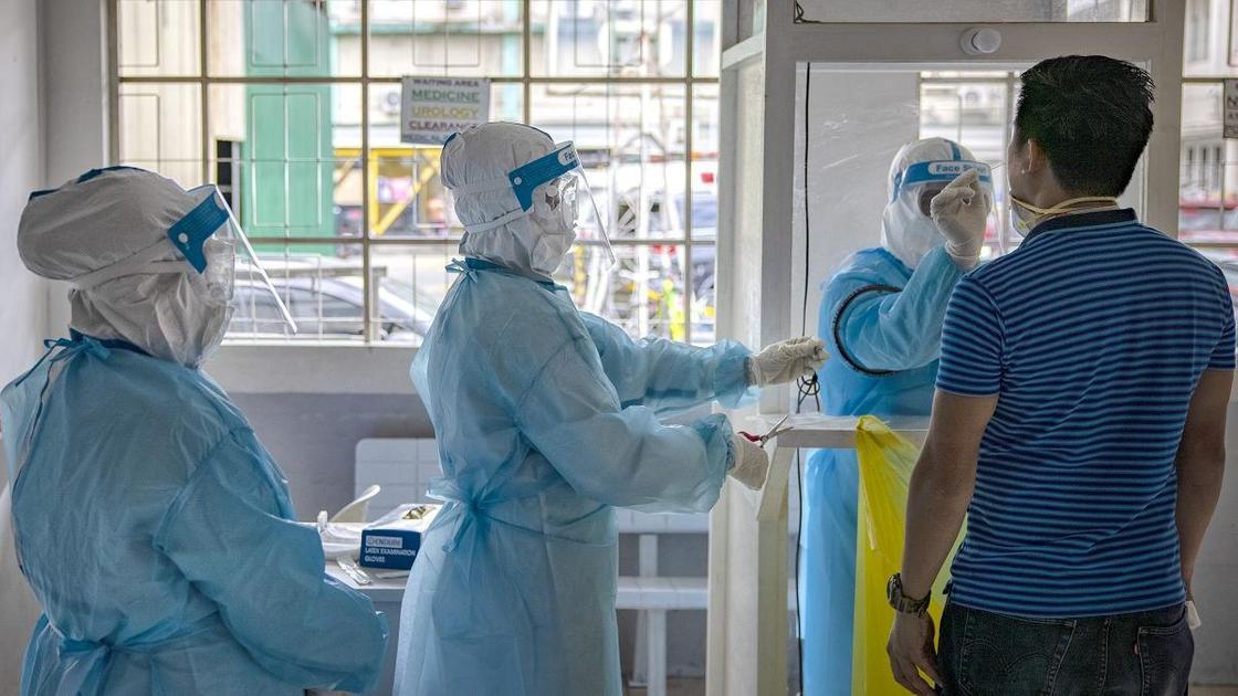 Медики в защитных костюмах берут у мужчины биоматериал для теста