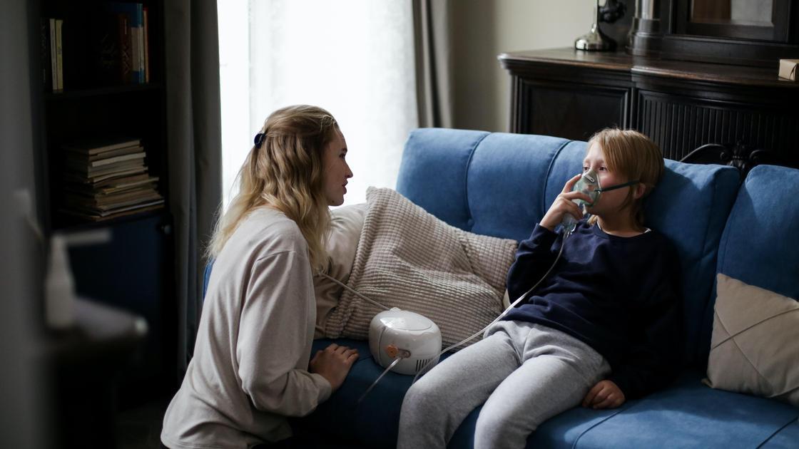 Женщина сидит возле мальчика с ингалятором
