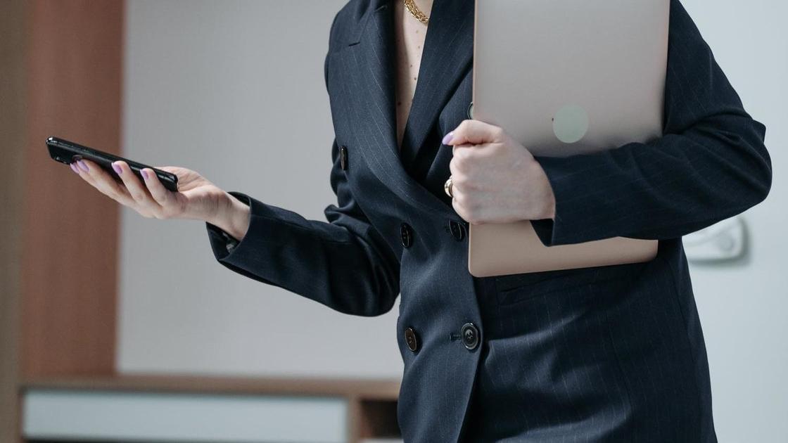 Женщина в костюме с телефоном в руках