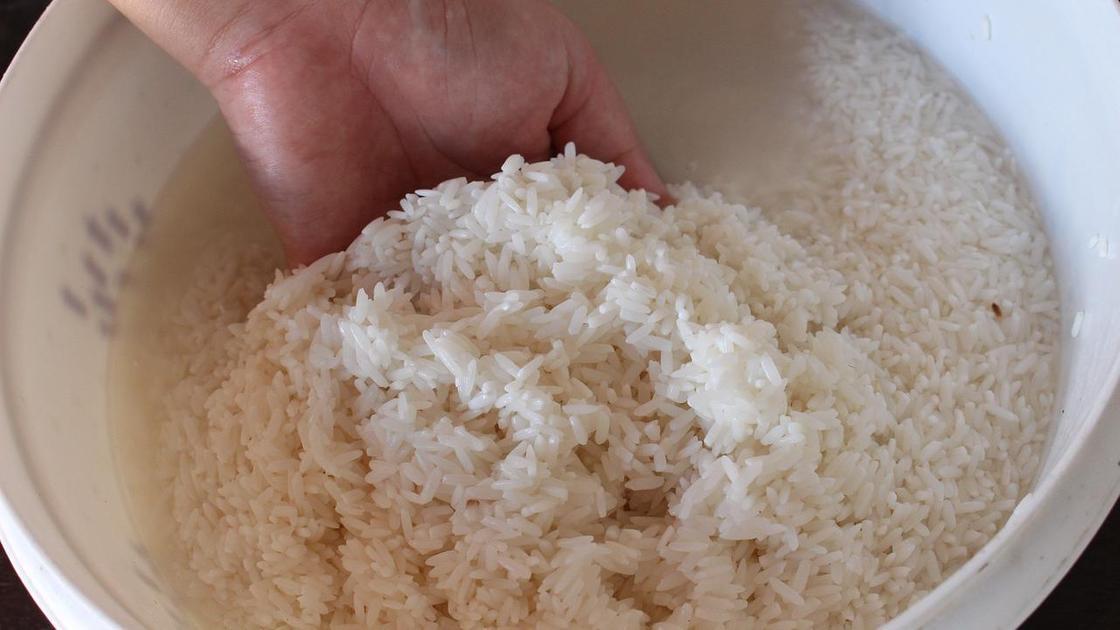 Человек промывает рис в миске с водой