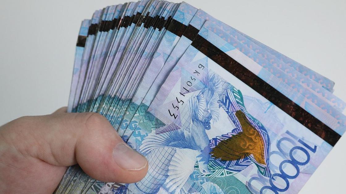 Мужчина держит в руке 10-тысячные купюры тенге