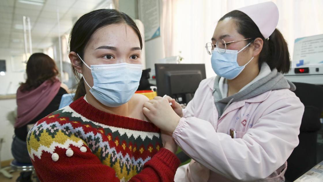 Медсестра ставит вакцину девушке
